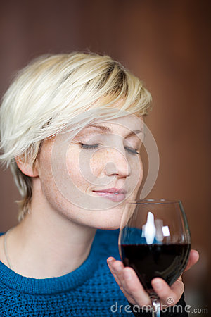 有红葡萄酒玻璃的年轻白肤金发的妇女