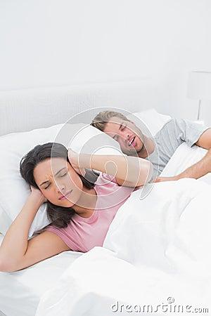 盖她的耳朵的妇女,当她的丈夫打鼾时