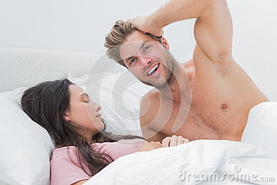 Без рубашки человек представляя рядом с его спать партнером