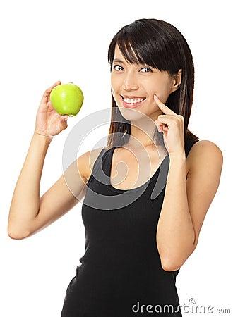 亚裔妇女用绿色苹果和暴牙的微笑
