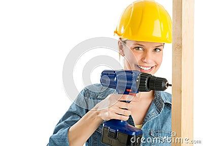 Рабочий-строитель используя электрическую дрель на деревянной планке