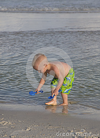 Ребенок играя в песке и прибое.