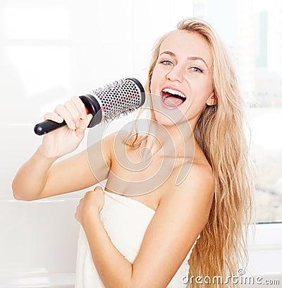 滑稽的女性唱在梳子的歌曲