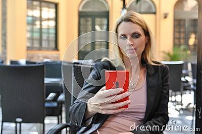 使用一个巧妙的电话的一个年轻女商人户外