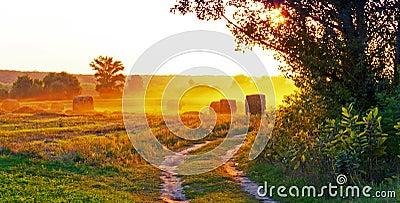 Заход солнца над полями, и солома.