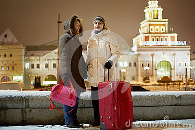 年轻加上大红色台车袋子在晚上站立