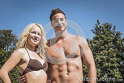 女孩和英俊的男孩佩带的游泳衣