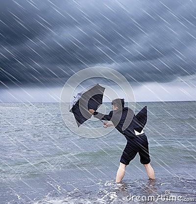 库存照片: 拿着伞的商人抵抗暴雨