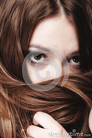 妇女由长的棕色头发盖面孔图片
