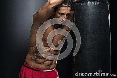 有纹身花刺的在红色拳击手套-在黑背景的拳击一个人-一种健康生活方