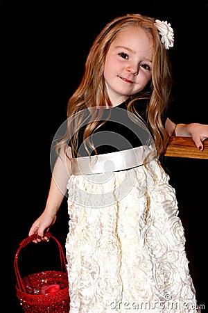 小眼睛明亮的五岁的女孩在她拿着一个红色篮子的长的头发穿一件俏丽的图片
