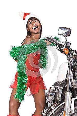 骑自行车盖帽头发长期查出的下红色圣诞老人给白人妇女.图片
