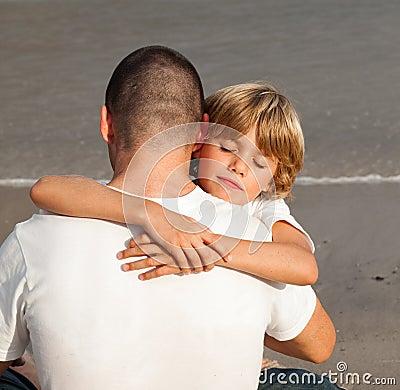 男孩父亲他拥抱的年轻人