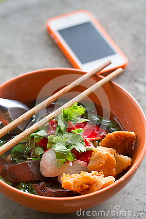 Noodles with fishball and vegetable with red sauce on table