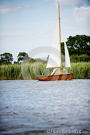 Norfolk Broads sail boat on a river by the bankment