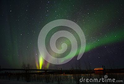 Northern light over a field with a cottage