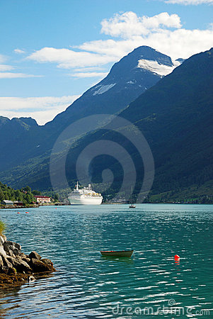 Norwegian fjord with white ferry on blue water.