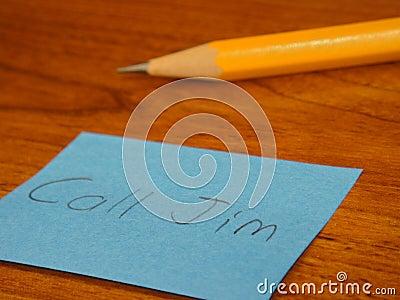 Nota y lápiz pegajosos en el escritorio