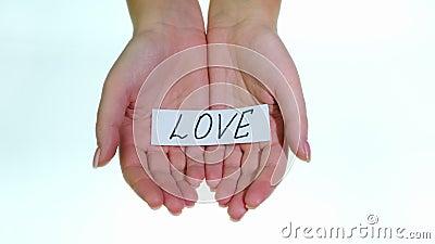 Note LOVE dans les mains des femmes sur fond blanc banque de vidéos