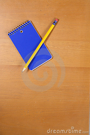 A Note pad and pencil on a desk