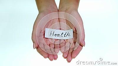 Note Santé entre les mains des femmes sur fond blanc banque de vidéos
