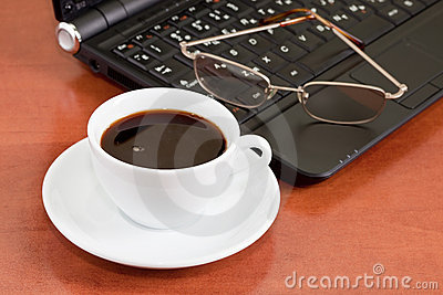 Notebook, glasses and cup of coffee