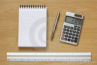 Notebook pen calculator and ruler on desk