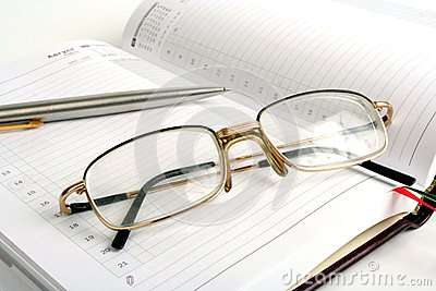 Notebook, pen and eyeglasses