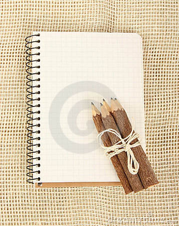 Notebook and pencils on burlap