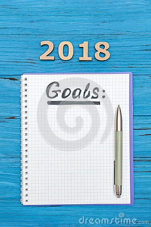 Free Notebook With New Years Goals For 2018 With A Pen And Numbers 2018 On A Blue Wooden Table Stock Images - 102772104