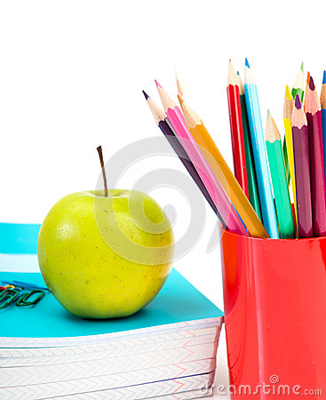 Notebooks, pencils and apple.