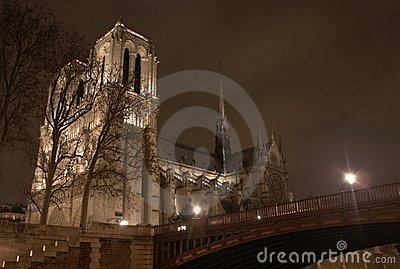 Notre Dame de Paris cathedral at night with bridge