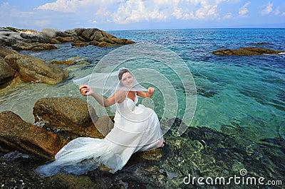 Novia hermosa que se sienta sobre el mar cristalino