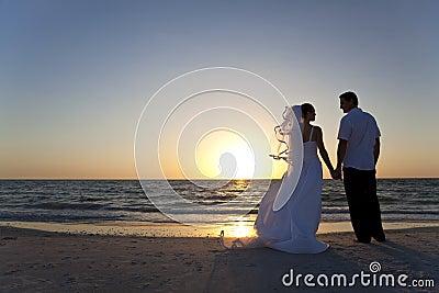 Novia y boda de playa casada novio de la puesta del sol de los pares
