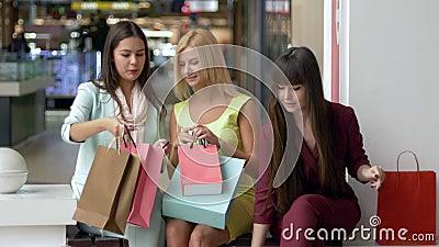 Novias en ropa colorida después de que haga compras discuta sus compras juntas mientras que se siente en la alameda durante negro almacen de video