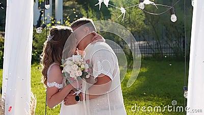 Novias y novios se besan entre ellos bajo el arco de la ceremonia de boda al aire libre Amigos disparan al confetti arriba de rec almacen de metraje de vídeo