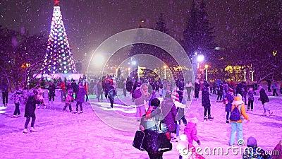 NOVOSIBIRSK, ΡΩΣΊΑ -25 Δεκεμβρίου 2019: Ο κόσμος κάνει παγοδρομία στο πάρκο της πόλης την παραμονή των Χριστουγέννων Χιονόπτωση απόθεμα βίντεο