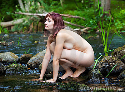 Nude woman and forest stream