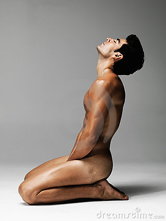 Nude young man posing against grey background