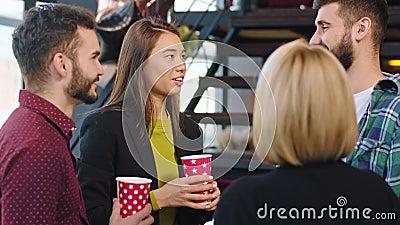Num moderno grupo de escritórios multiétnicos, enquanto fazem uma pausa para café, têm uma conversa amigável sorrindo filme