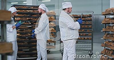 Numa indústria de padaria, principal padeiro tirando fotos de um tablet de nova tecnologia de um pão fresco cozido de prateleiras vídeos de arquivo