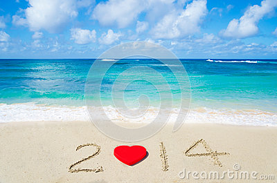Number 2014 with heart shape on the sandy beach