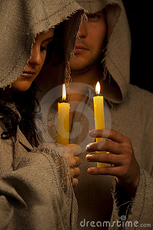 Nun and monk praing with candles