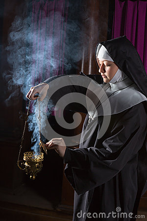 Nun preparing incense for mass