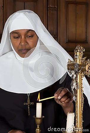 Nunna som tänder en stearinljus