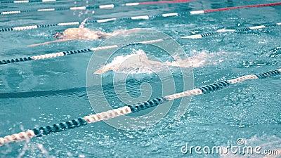 Nuotatori dell'angolo alto tre che hanno concorrenza nella piscina che segue colpo archivi video