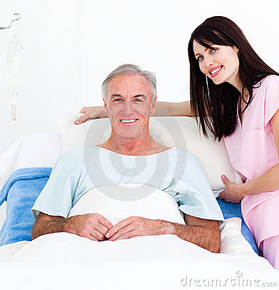 A nurse adjusting pillows for a senior patient