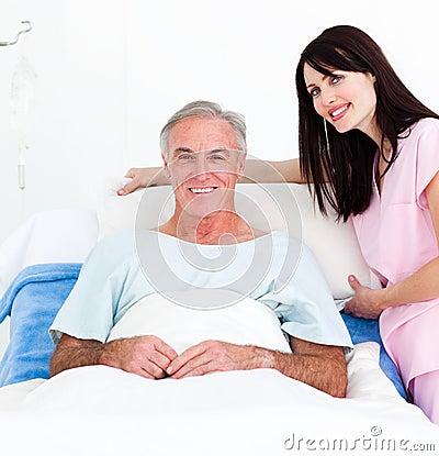A nurse adjusting pillows for a senior patient
