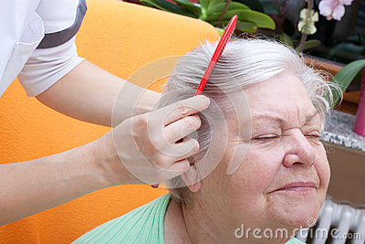 Nurse combing senior through her hair