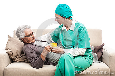 Nurse giving pills to old sick woman